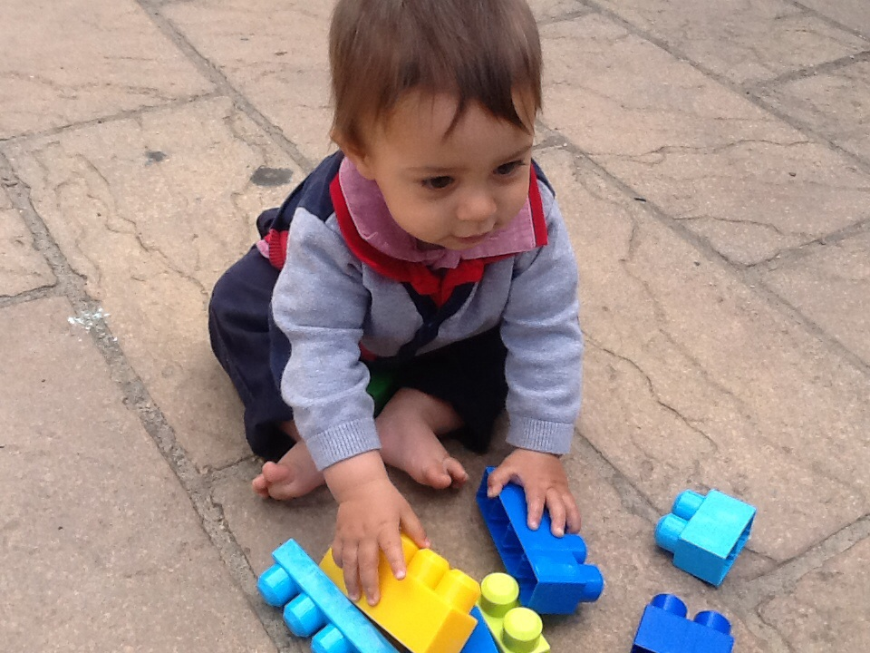 The beginning of the learning story: small child examining building blocks