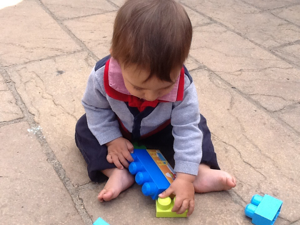 Image showing the second learning story photo, a young child putting blocks together