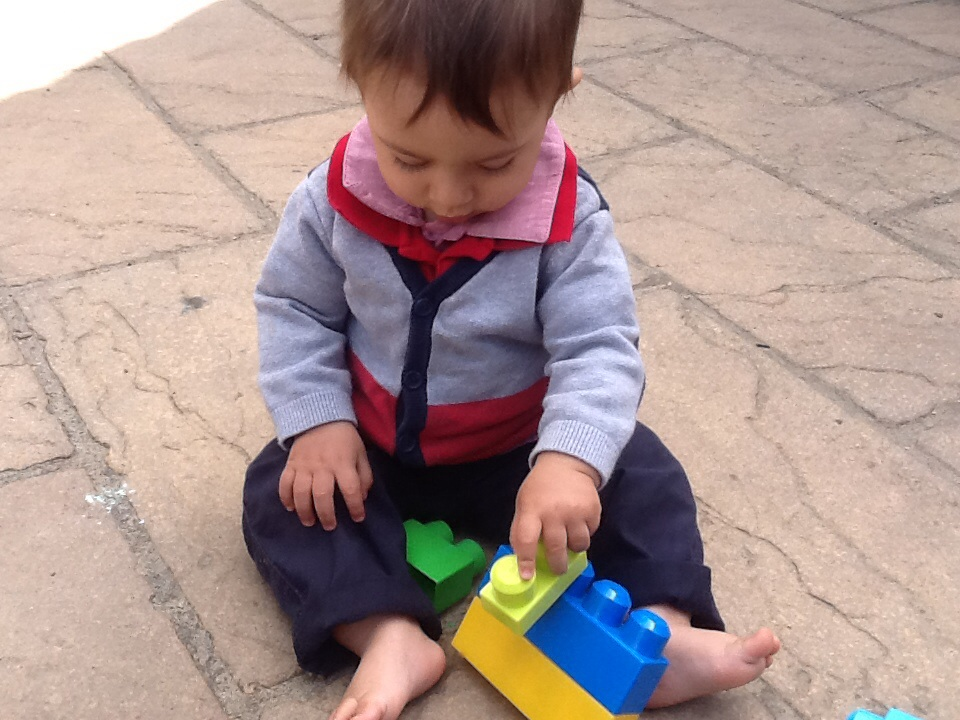 Image showing the third learning story photo, young child building a taller tower of blocks
